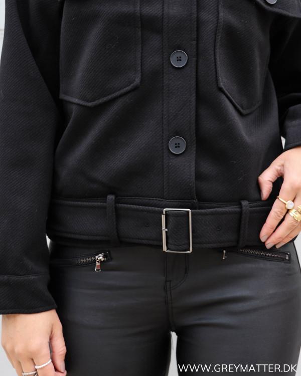 Sort jakke til damer med rå detaljer