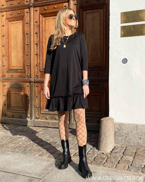 Sort kjole med flæsekant forneden