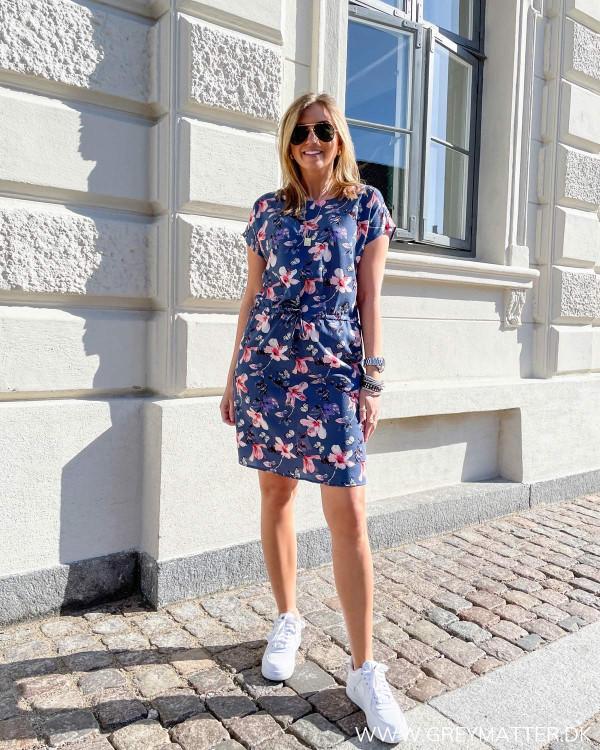 Sommerkjole med blomsterprint stylet med hvide sneaks