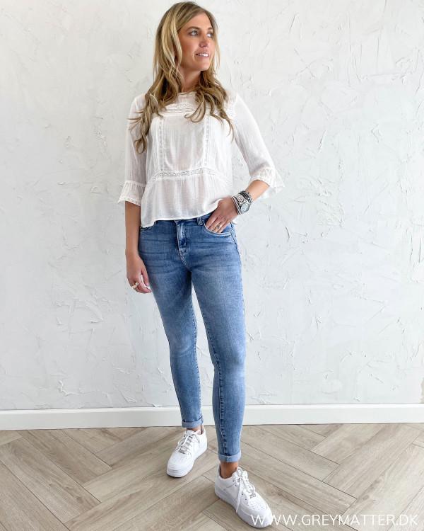 Hvid sommerbluse stylet med blå cowboy bukser til damer