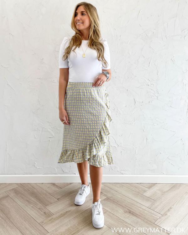 Ternet nederdel fra Vila stylet med hvid tee og Nike sneaks