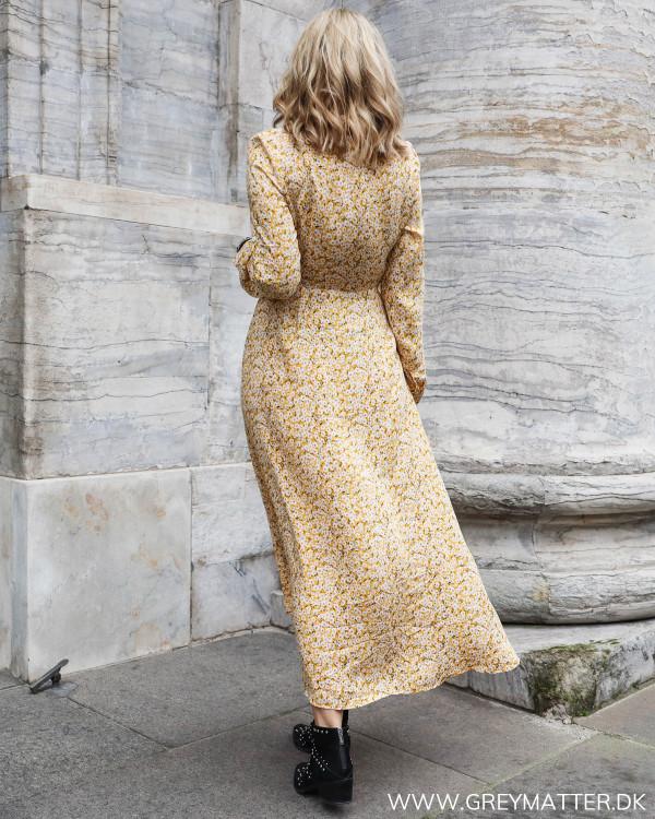 Lang kjole med blomsterprint i gule farver set bagfra