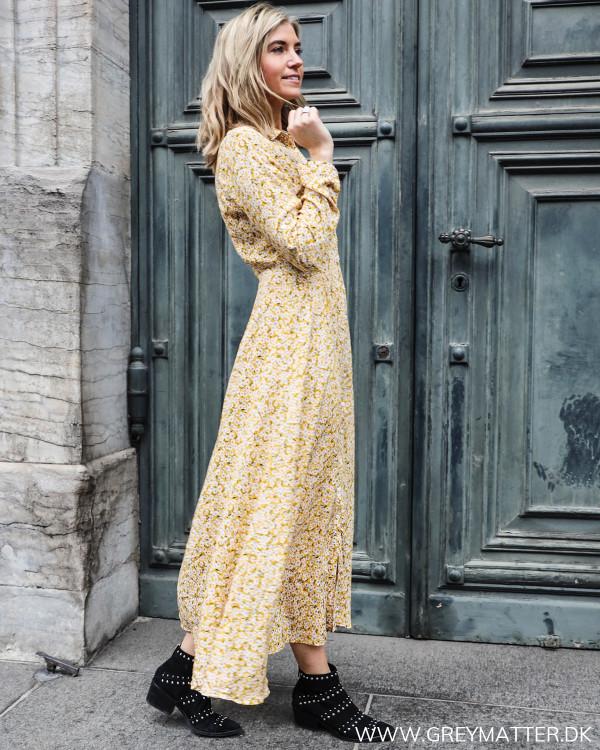 Lang kjole med blomsterprint i gule farver set fra siden