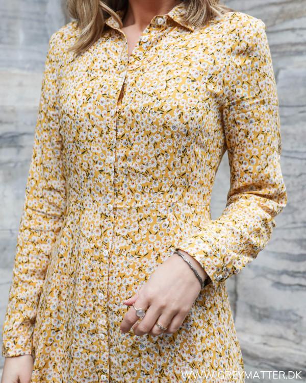 Lang kjole med blomsterprint i gule farver set tæt på