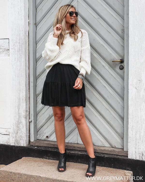 Sort nederdel i mesh stylet med en hvid loose-fit strik bluse