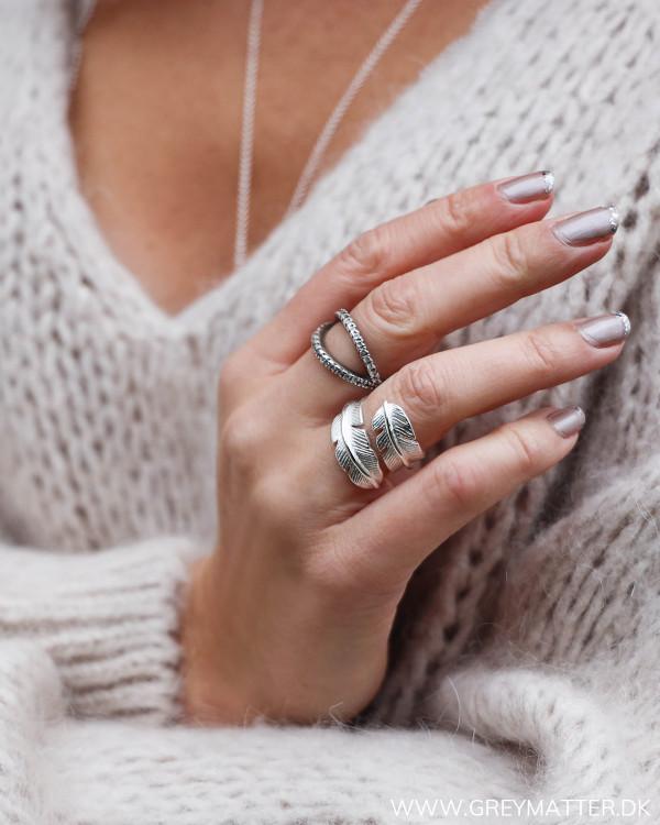 Fjerring i sølv set på finger forfra