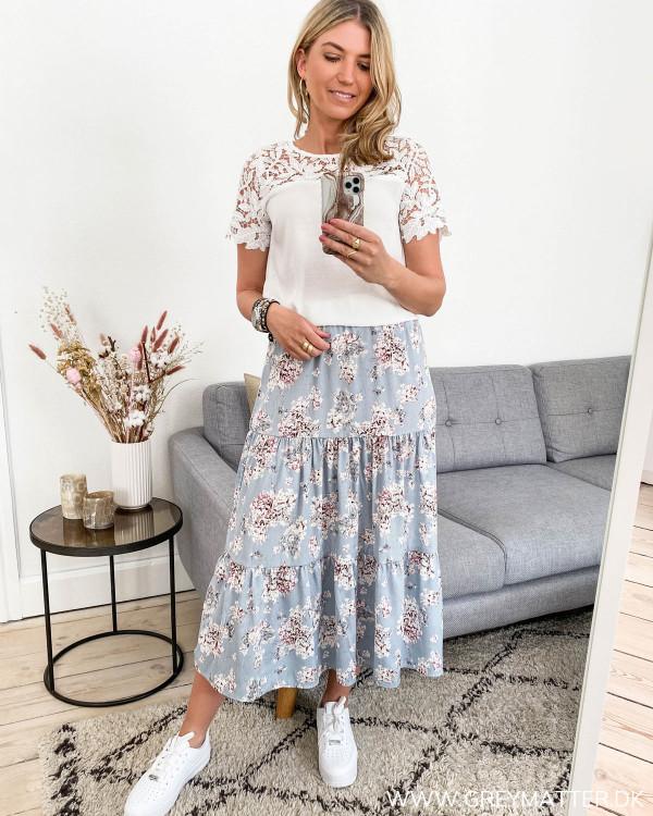 Blå nederdel med blomsterprint, set i hel figur