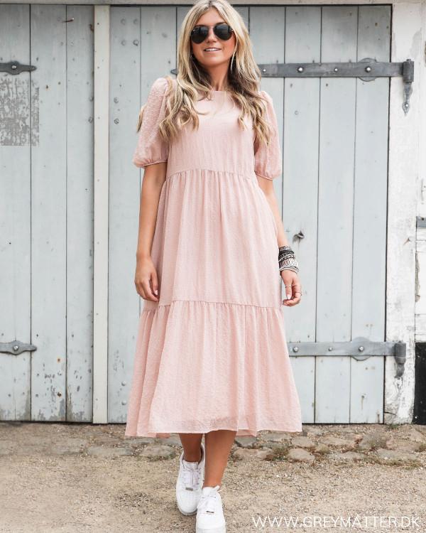 Smuk lyserød kjole fra Vila set forfra stylet med hvide Nike sneaks
