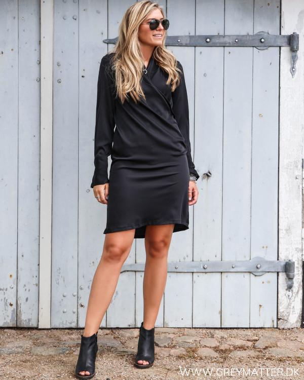 Sort Karmamia kjole stylet med høje sko og et smykke