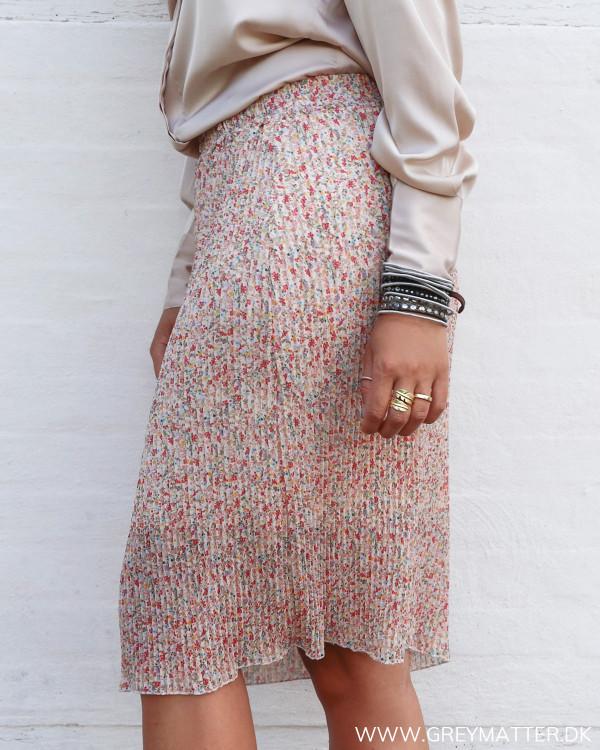 Plissé nederdel med blomsterprint set fra siden